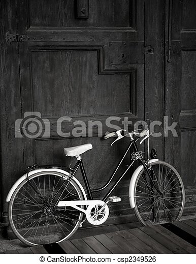 Aged vintage black bicycle big wooden door black and white csp2349526