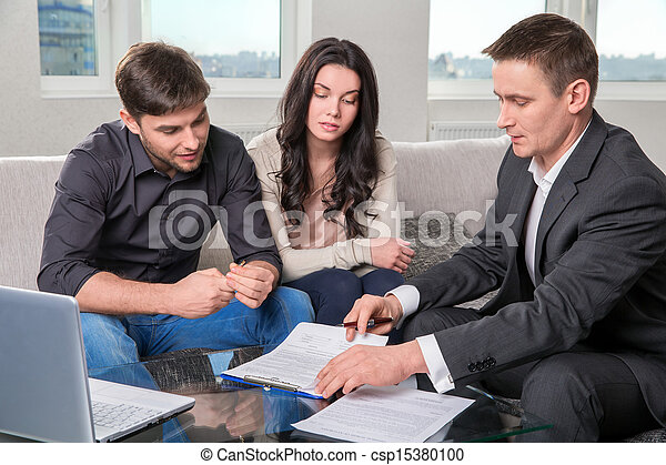 Agent advises the couple, signing documents - csp15380100
