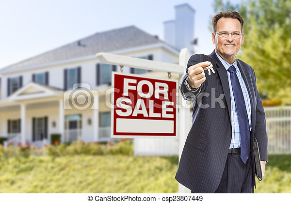 Agent with Keys in Front of Sale Sign and House - csp23807449