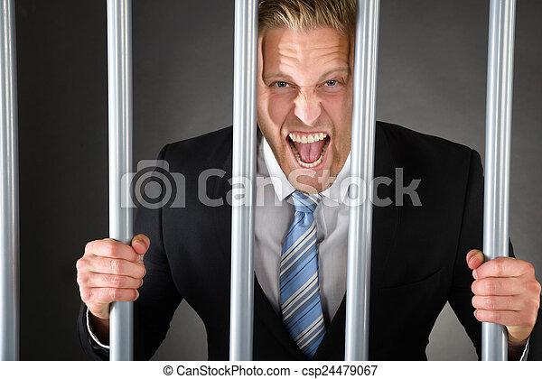 Aggressive Businessman Behind Bars - csp24479067