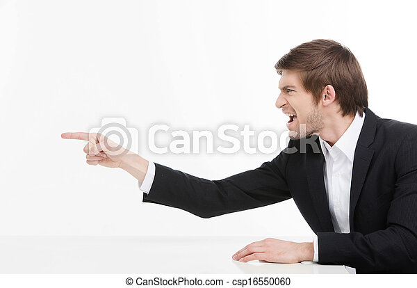 Aggressive businessman. Side view of angry young businessman shouting and pointing away while isolated on white - csp16550060