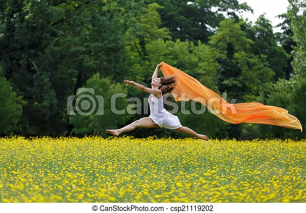 Agile woman leaping in the air trailing a scarf - csp21119202