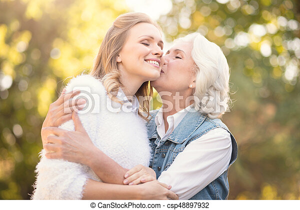 aging mother kissing loving daughter in the park giving love to my