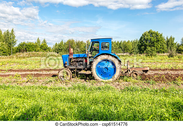 Agricultural tractor working at the potato field - csp61514776