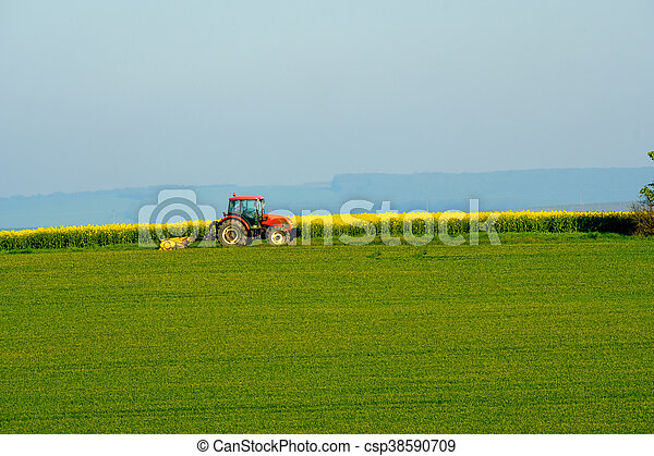 Agricultural tractor working in a countryside - csp38590709