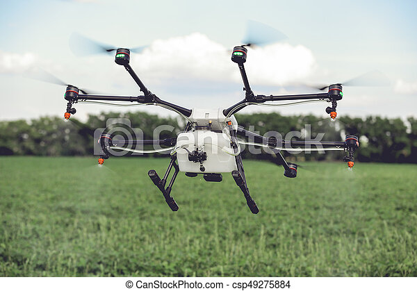 Agriculture drone spraying water or pesticides to grow over green field