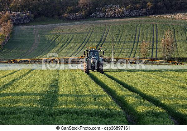 Agriculture - Farmer Spraying Crops - csp36897161