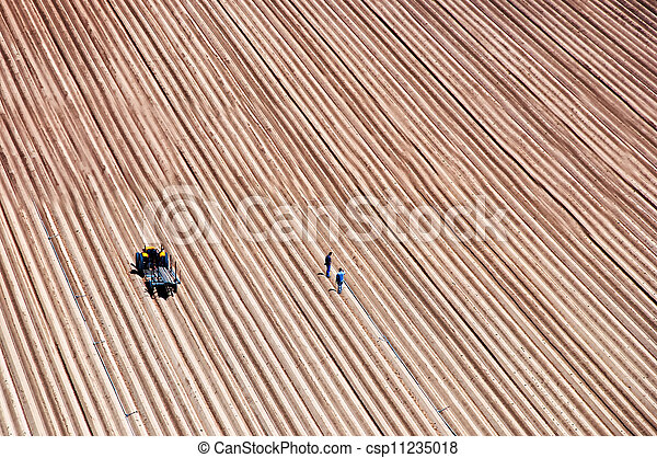 Agriculture field lines and two farmers with tractor - csp11235018