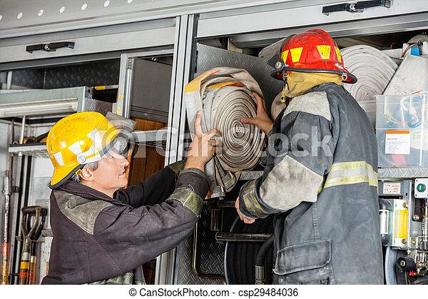 Bomberos quitando la manguera del camión - csp29484036