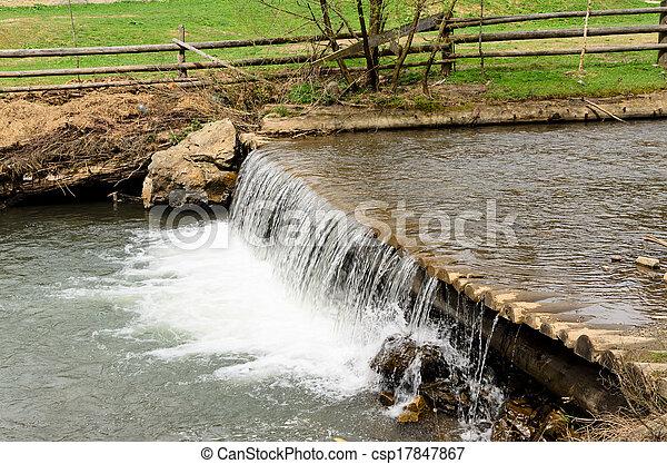 Agua en un arroyo que pasa por encima de una presa - csp17847867