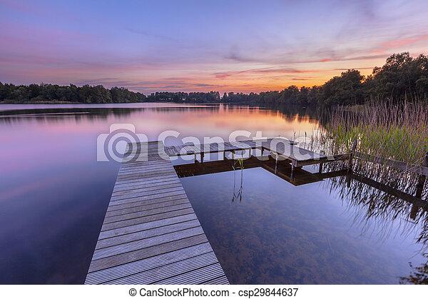 El atardecer sobre el agua serena de un lago - csp29844637