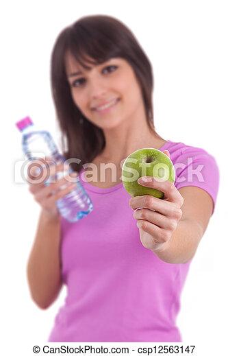 Una joven caucásica sosteniendo una botella de agua y una manzana - csp12563147
