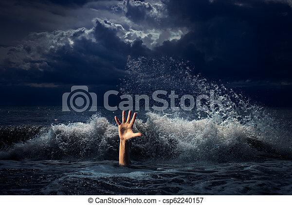 Un hombre ahogado con la mano en agua del mar - csp62240157