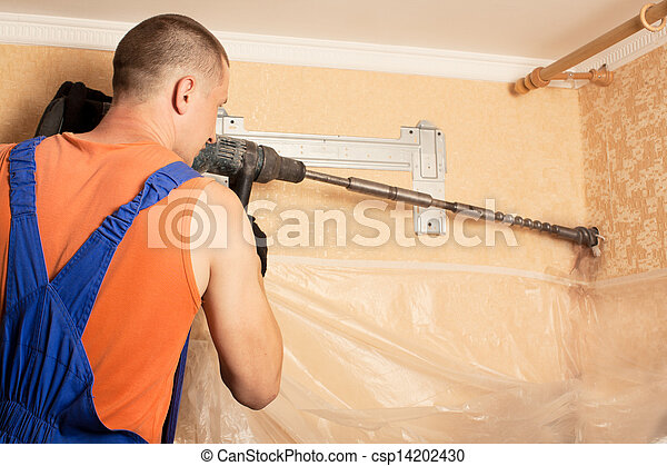 Air conditioning master preparing to install new air conditioner. drilling the wall. - csp14202430