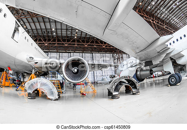 Aircraft in the hangar repair and maintenance, view from under the wing of the airplane. - csp61450809