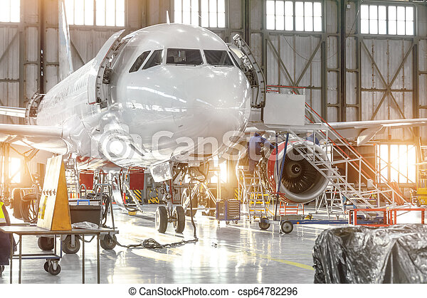 Aircraft jet on maintenance of engine and fuselage check repair in airport hangar. - csp64782296