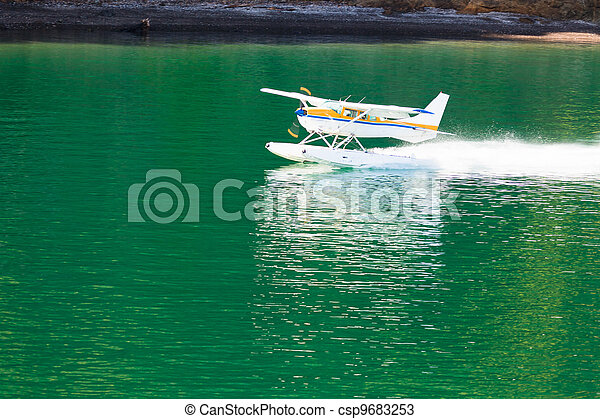 Aircraft seaplane taking off on calm water of lake - csp9683253