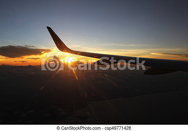 view from window of airplane, aircraft wing flying over beautiful sunlight