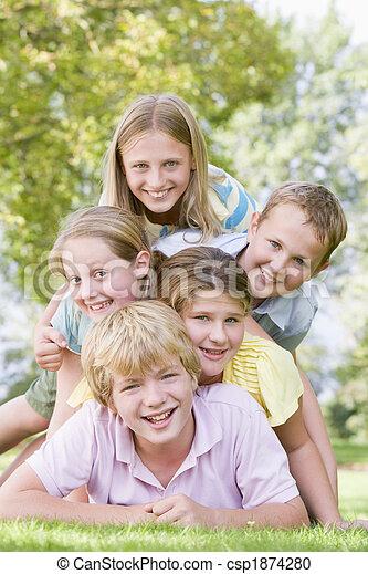 Cinco jóvenes amigos apilados al aire libre sonriendo - csp1874280