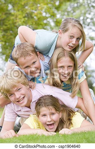 Cinco jóvenes amigos apilados al aire libre sonrientes - csp1904640