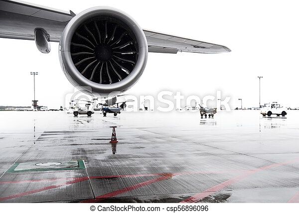 airliner jet wing and engine on airport apron on rainy day - csp56896096