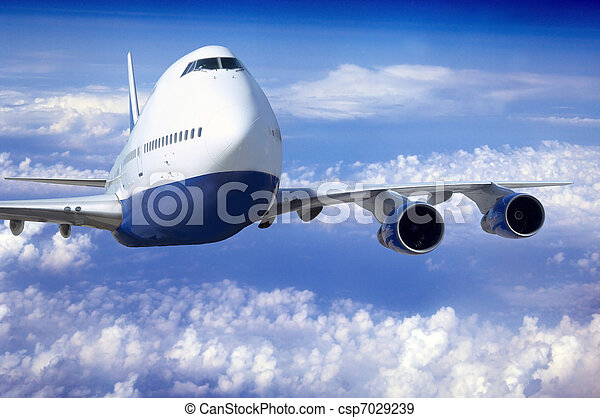 Airplane at fly on the sky with clouds - csp7029239