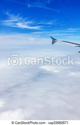 Airplane flight - window view over the clouds - csp33682871