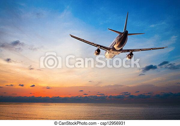 Airplane flying at sunset  - csp12956931