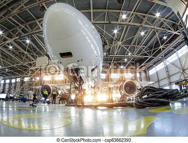Airplane in the hangar for maintenance, bottom nose view. - csp63662393