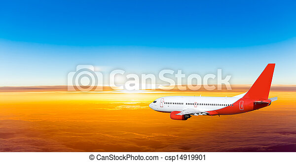 Airplane in the sky at sunset. A passenger plane in the sky - csp14919901