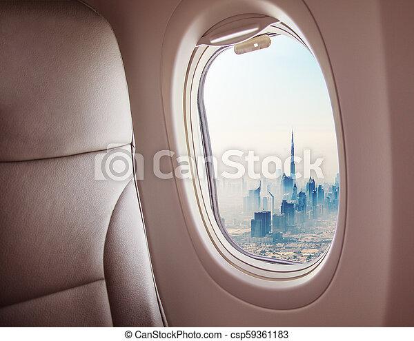 Airplane interior with window view of Dubai city - csp59361183