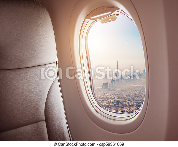 Airplane interior with window view of Dubai city - csp59361069
