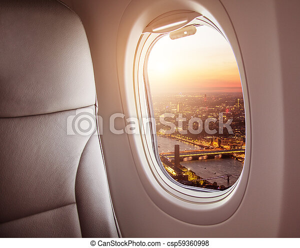 Airplane interior with window view of London city, Europe. - csp59360998