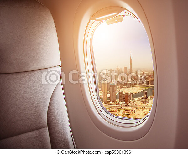 Airplane interior with window view of Dubai city - csp59361396
