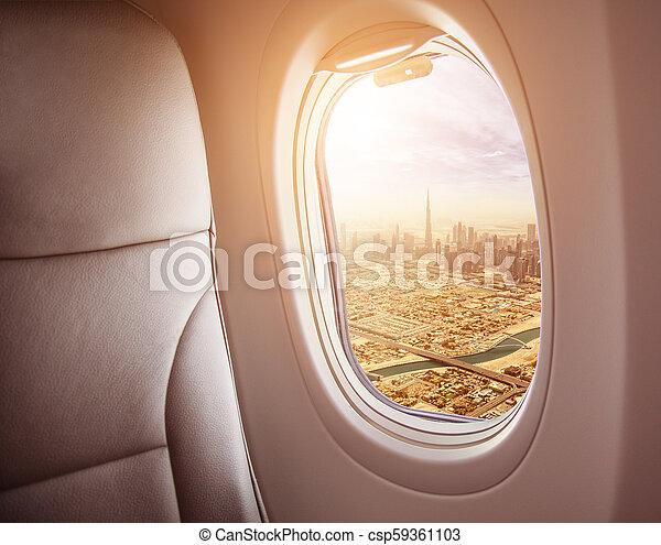 Airplane interior with window view of Dubai city - csp59361103