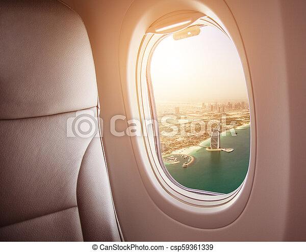Airplane interior with window view of Dubai city - csp59361339