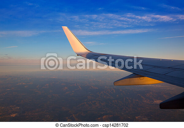 Airplane jet wing at sunset with golden sunlight - csp14281702