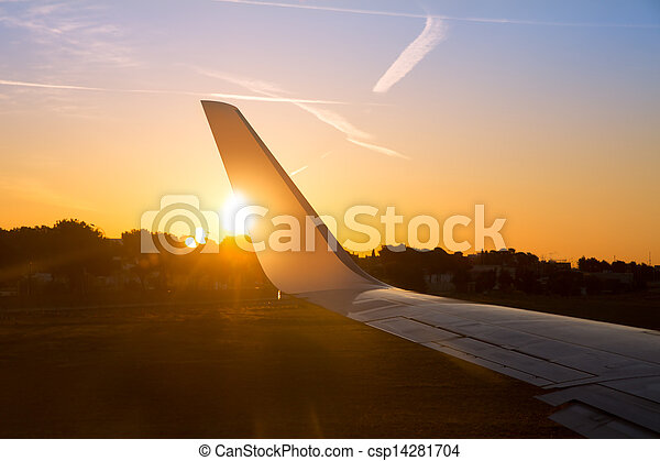 Airplane jet wing at sunset with golden sunlight - csp14281704