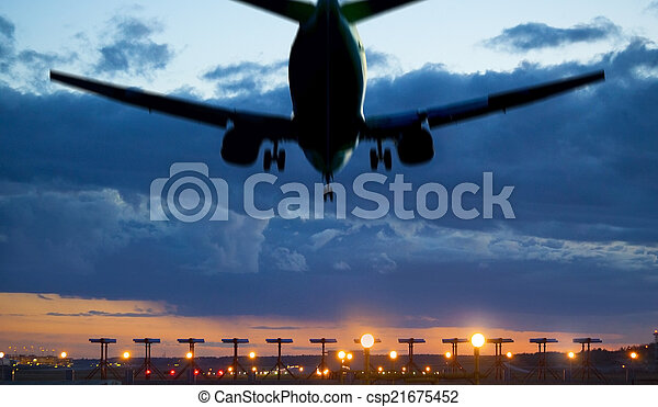 Airplane landing  at dusk - csp21675452