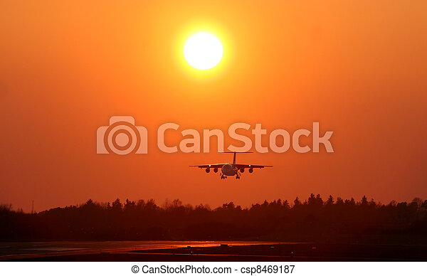 Airplane landing at sunset - csp8469187