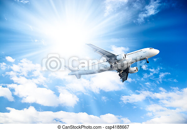 Airplane on blue sky and bright sun background - csp4188667