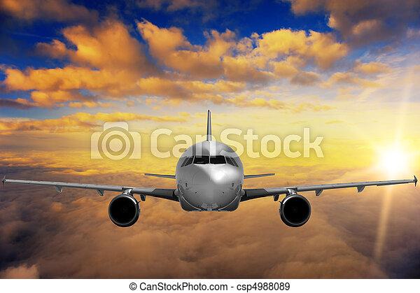 Airplane on sunset sky - csp4988089