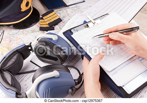 Airplane pilot filling in flight plan - csp12975367