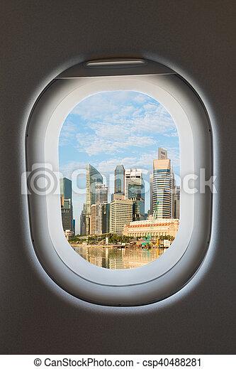 Airplane window and modern city skyline. - csp40488281