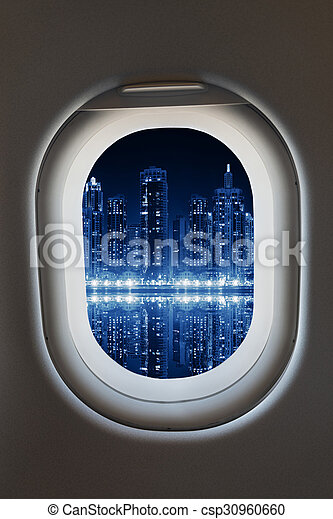 Airplane window from interior of aircraft with modern city view.  - csp30960660