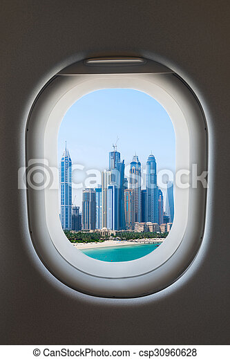 Airplane window from interior of aircraft with modern city view.  - csp30960628