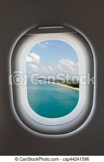 Airplane window from interior of aircraft and tropical beach. - csp44241596