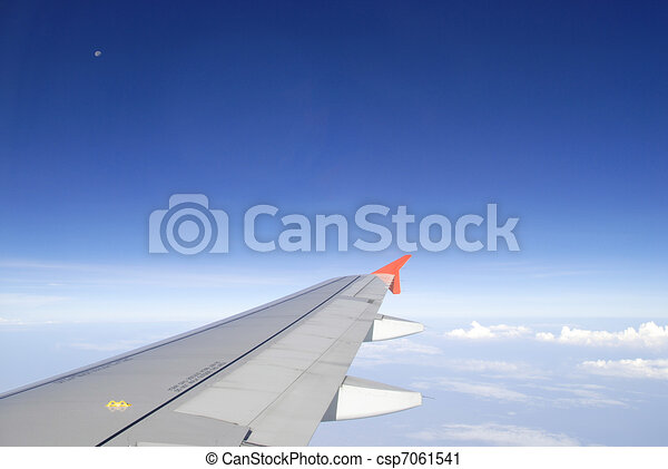 Airplane wing in the blue sky - csp7061541