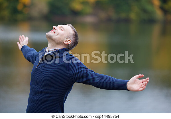 Hombre con brazos extendidos al aire libre - csp14495754