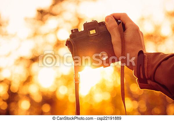 Man hand sosteniendo una cámara retro fotofonica al aire libre estilo de vida con luces solares naturaleza otoñal bokeh en el fondo - csp22191889